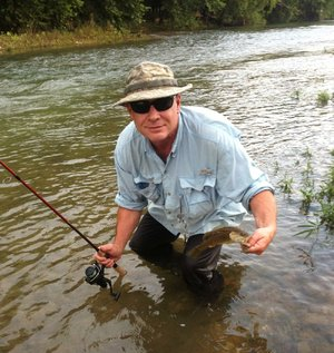 Rusty Pruitt of Bryant shows a typical smallmouth he caught Friday while fishing on Crooked Creek near Yellville.  Water levels were high but dropping during the trip.