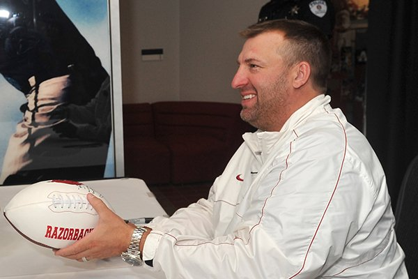 Arkansas coach Bret Bielema signs autographs during the Razorbacks' fan day on Sunday, Aug. 18, 2013 at Bud Walton Arena in Fayetteville.