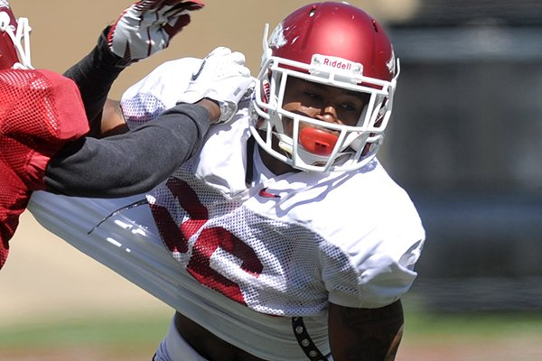 Arkansas safety Rohan Gaines battles receiver Mekale McKay during an April 6, 2013 practice at Razorback Stadium in Fayetteville.