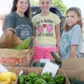 Kristy Tipton and daughters, Haley, 14, and Reagan, 10, offer farm-raised produce for sale in the pa...