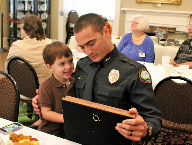 officer-jeremy-palmer-looks-at-the-noel-don-mcguire-award-with-his-son-4-year-old-jayden-after-receiving-the-honor-at-a-ceremony-thursday