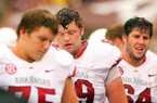 Arkansas' ofensive lineman Luke Charpentier, left, David Hurd, and Travis Swanson, right, head back to the bench during the second half of thier loss to Texas A&M during the second quarter of their game Saturday, Sept. 29, 2012 in College Station, Texas.