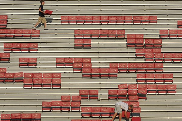 Fayetteville High School Students Logan Schwartz, junior, (bottom) and Brett Bonine, senior, work on installing the seat backs at Razorback Stadium Saturday August 24th in Fayetteville. The Razorbacks are scheduled to open the season Saturday at the stadium against Louisiana-Lafayette.