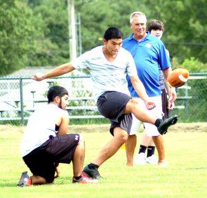 Allan Castaneda (left) held the football for kicker, Meng Vang (center). As the football began its ascent toward the goal post, head football coach, Shane Holland, analyzed Vang's technique. Holland put his players through their paces during practice Aug. 19 in Bulldog Stadium. The first game will be a benefit match with Gentry on Aug. 29, at Decatur.