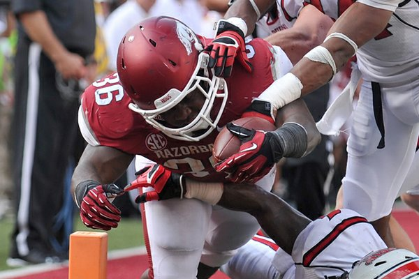Arkansas fullback Kiero Small pushes his way past Louisiana-Lafayette defenders to score a touchdown Saturday at Donald W. Reynolds Razorback Stadium in Fayetteville.