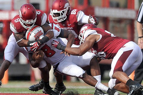 University of Arkansas defenders Tevin Mitchel, Brandon Lewis and Trey Flowers take down Louisiana-Lafayette quarterback Terrance Broadway during the third quarter of Saturday afternoon's game at Razorback Stadium in Fayetteville.