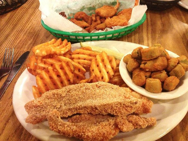 the-seafood-plate-at-grampas-is-a-two-dish-affair-that-includes-a-basket-of-fried-clam-strips-a-stuffed-crab-and-three-fried-shrimp-background-and-a-plate-with-two-catfish-fillets-and-two-sides-for-example-waffle-fries-and-fried-okra