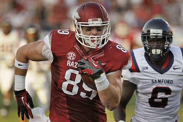 Arkansas tight end Mitchell Loewen (89) runs into the end zone ahead of Samford defensive back Jaquiski Tartt (6) during the first quarter of an NCAA college football game in Little Rock, Ark., Saturday, Sept. 7, 2013. (AP Photo/Danny Johnston)