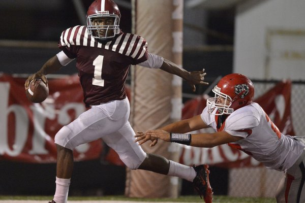 Pine Bluff quarterback Ladarius Skelton (1) avoids a Fort Smith Northside defender in the fourth quarter Friday in Pine Bluff. Skelton rushed 22 times for 93 yards and a touchdown and was 10 of 15 passing for 156 yards and 2 touchdowns as the teams fought to a 31-31 tie.