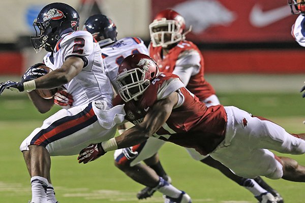 Arkansas' Chris Jones (41) lays out to get Samford's Fabian Truss (2) during their game at War Memorial Stadium in Little Rock Saturday.