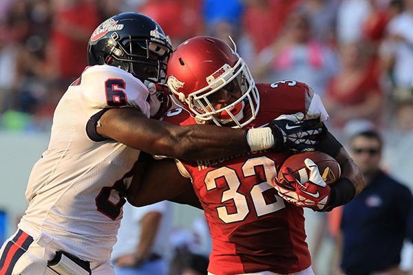 Arkansas's Jonathan Williams (32) is caught after a long run by Samford's Jaquiski Tartt (6) during their game at War Memorial Stadium in Little Rock Saturday.