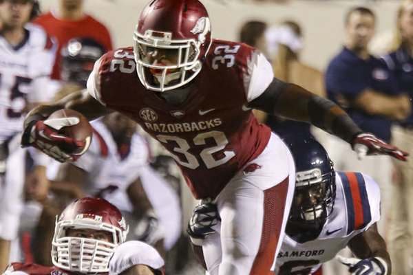 Arkansas running back Jonathan Williams gets past Samford Bulldogs' Jaquiski Tartt, right, during their game September 7, 2013 at War Memorial Stadium.