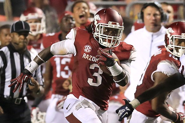 Arkansas running back Alex Collins (3) runs for a 55-yard gain against Samford on Saturday, Sept. 7, 2013 at War Memorial Stadium in Little Rock.