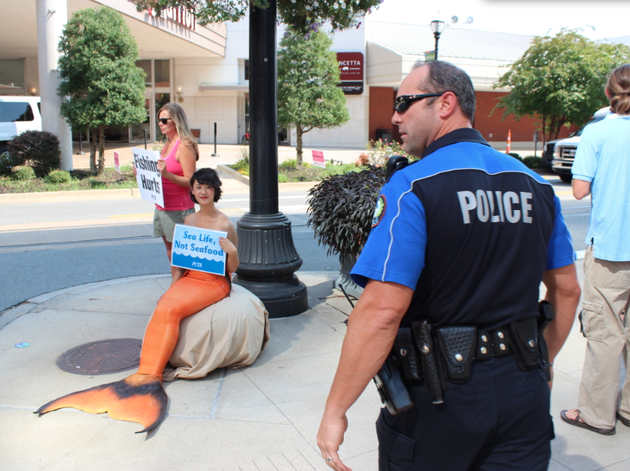 a-police-officer-tells-protesters-with-peta-including-one-dressed-as-a-mermaid-and-bystanders-to-keep-the-sidewalk-in-the-area-clear-for-pedestrians-tuesday-morning-in-little-rock