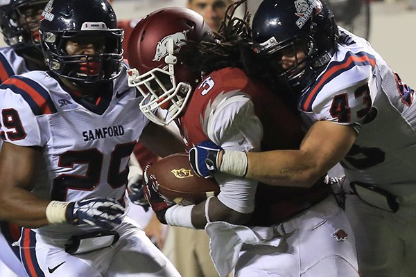 Arkansas' Alex Collins (3) carries a host of Samford players including Josh Killett (43) after a long run during their game at War Memorial Stadium in Little Rock Saturday.