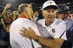 In this Sept. 10, 2011, file photo, South Carolina coach Steve Spurrier, right, and Georgia coach Mark Richt meet at midfield after South Carolina's on 45-42 in an NCAA college football game in Athens, Ga.