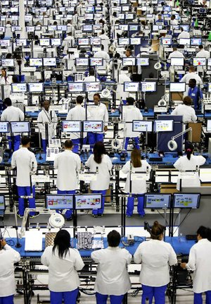 Employees assemble Motorola Solutions Inc. Moto X smartphones at the Flextronics International Ltd. factory in Fort Worth on Tuesday. More than 2,000 Flextronics International Ltd. employees have been contracted to manufacture the smartphone.