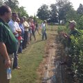 Guy Ames, right, explains his techniques for growing pears and apples to a tour group in Fayettevill...