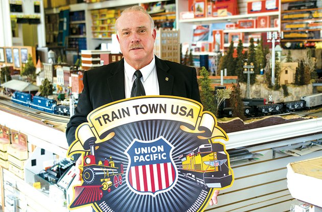 craig-christiansen-holds-a-sign-denoting-the-inclusion-of-the-bald-knob-depot-in-union-pacifics-train-town-usa-registry