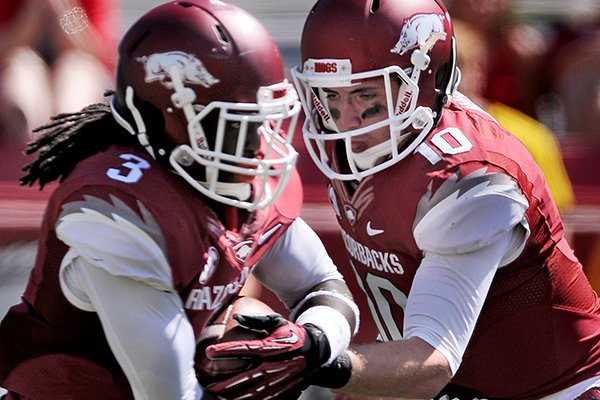 Arkansas quarterback Brandon Allen hands the ball off to running back Alex Collins in the first quarter of the game in Razorback Stadium in Fayetteville on Saturday, Sept. 14, 2013.