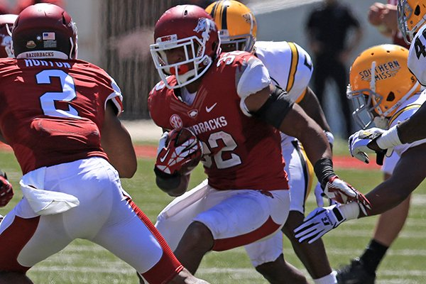 Arkansas' Jonathan Williams (32) cuts behind the block of Julian Horton (2) against Southern Miss defenders in the 4th quarter during their game Saturday at Reynolds Razorback Stadium in Fayetteville.