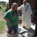 Kristi Pfeiffer of Paris carries on the tradition of being the first to stomp the grapes Saturday at...