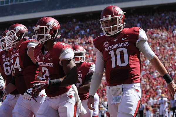 Arkansas quarterback Brandon Allen (10) heads to the sidelines after scoring a touchdown but injuring his shoulder Saturday, Sept. 14, 2013, during the first quarter of play at Razorback Stadium in Fayetteville.