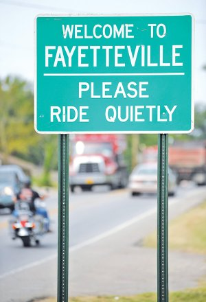 A motorcyclist rides Tuesday past a sign along East Huntsville requesting cyclists to ride quietly as the enter Fayetteville.
