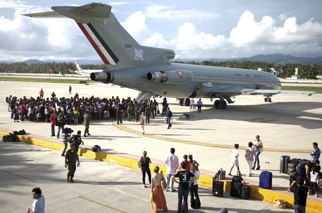 hundreds-of-stranded-tourists-gather-around-a-mexican-air-force-jet-as-they-wait-to-be-evacuated-at-the-air-base-in-pie-de-la-cuesta-near-acapulco-mexico-on-tuesday-sept-17-2013