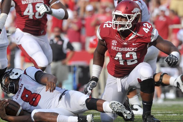 Arkansas defensive end Chris Smith reacts after sacking Louisiana-Lafayette quarterback Terrance Broadway during the first quarter of play Aug. 31, 2013 at Razorback Stadium in Fayetteville.