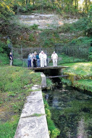 Officials with the Arkansas Game & Fish Commission and Illinois River Watershed Partnership gaze Wednesday at clear spring water spilling from a cave entrance in Cave Springs where Game & Fish will build education facilities and possibly a regional office. About 50 Game & Fish and partnership representatives toured the 30-acre site that was formerly Lake Keith.