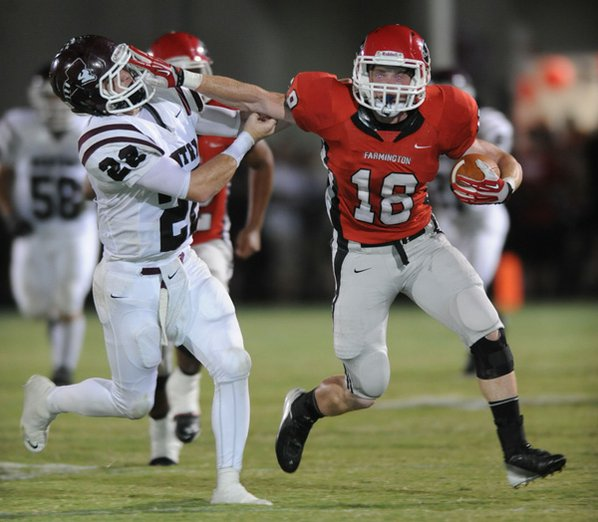Farmington's Chas Turner (18) fends ...