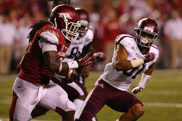 Arkansas running back Alex Collins runs during the first half of Saturday's game against Texas A&M at Razorback Stadium in Fayetteville.