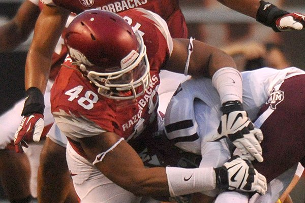 Arkansas defender Deatrich Wise Jr. takes down Texas A & M quarterback Johnny Manziel in the 1st quarter of Saturday night's game at Razorback Stadium in Fayetteville.