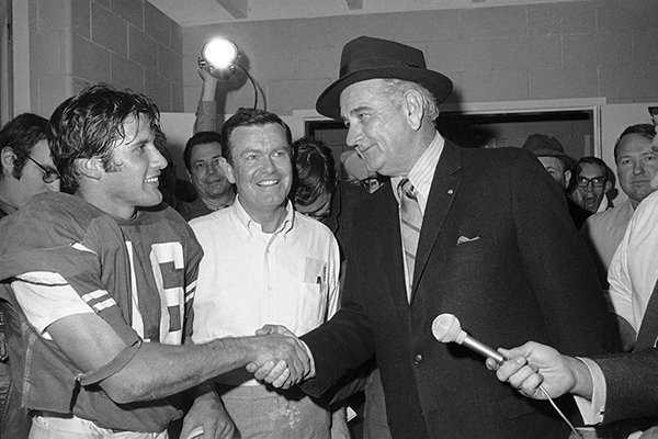 This Jan. 1, 1970 file photo shows former President Lyndon B. Johnson congratulating University of Texas quarterback James Street and coach Darrell Royal, center, in the dressing room after the Longhorns defeated Notre Dame in the Cotton Bowl in Dallas. (AP Photo/File)