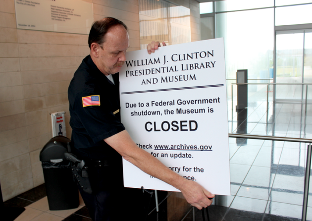 brian-mebert-a-security-officer-at-the-clinton-presidential-center-adjusts-a-sign-tuesday-oct-1-2013-alerting-visitors-that-the-center-is-closed-because-of-the-federal-government-shutdown