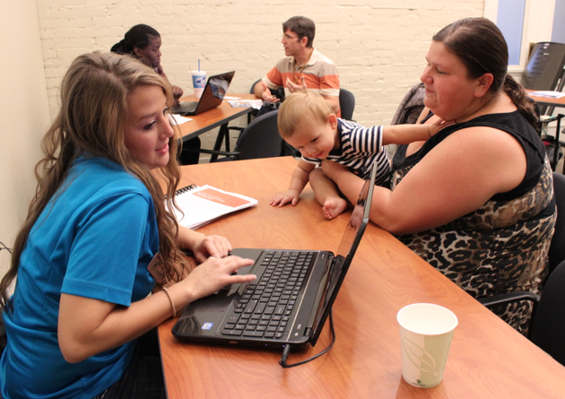 liz-davenport-of-north-little-rock-works-with-britney-sidebottom-of-the-arkansas-healthcare-access-foundation-to-enroll-in-the-healthcare-marketplace-while-her-son-1-year-old-logan-davenport-looks-on-tuesday-at-the-clinton-school