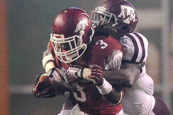 Arkansas running back Alex Collins is pulled down by Texas A&M defender Tramain Jacobs in the fourth quarter of Saturday night's game at Razorback Stadium in Fayetteville.