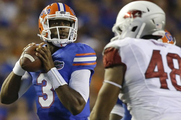 Florida quarterback Tyler Murphy (3) looks for a receiver as he is rushed by Arkansas defensive end Deatrich Wise Jr. (48) during the first half of an NCAA college football game in Gainesville, Fla., Saturday, Oct. 5, 2013.(AP Photo/John Raoux)