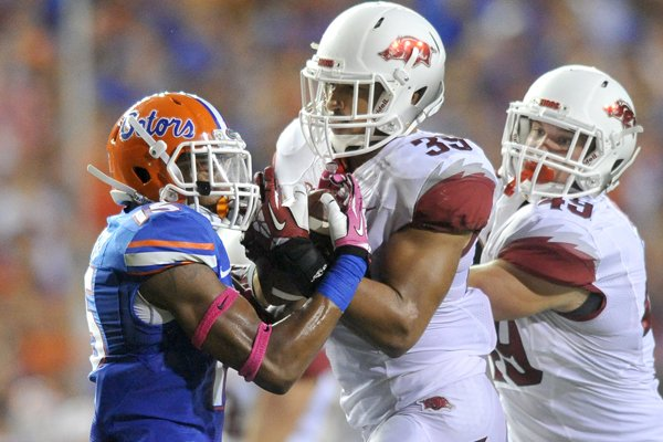 Arkansas defender Jarrett Lake catches a punt muffed by Florida punt returner Louchelz Purifoy. Lake was called for a penalty on the play during Saturday night's game at Ben Hill Griffin Stadium in Gainesville, Florida.