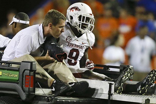 Arkansas cornerback Will Hines is taken off the field after he broke his arm during the second half of an NCAA college football game against Florida in Gainesville, Fla., Saturday, Oct. 5, 2013.(AP Photo/John Raoux)