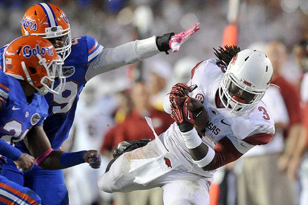 Arkansas Alex Collins pulls in a pass past Florida defender Darin Kitchens during the 3rd quarter of Saturday night's game at Ben Hill Griffin Stadium in Gainesville, Florida.