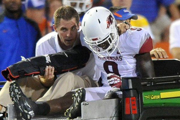 Arkansas cornerback Will Hines is carted off the field after injuring his arm Saturday at Ben Hill Griffin Stadium in Gainesville, Florida.