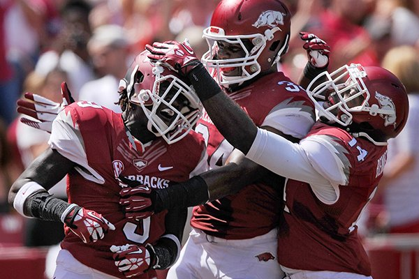 Arkansas defenders Eric Bennett, from right, and Braylon Mitchell celebrate with cornerback Will Hines intercepted a Southern Miss pass in the second quarter of the game in Razorbacks Stadium in Fayetteville on Saturday September 14, 2013.