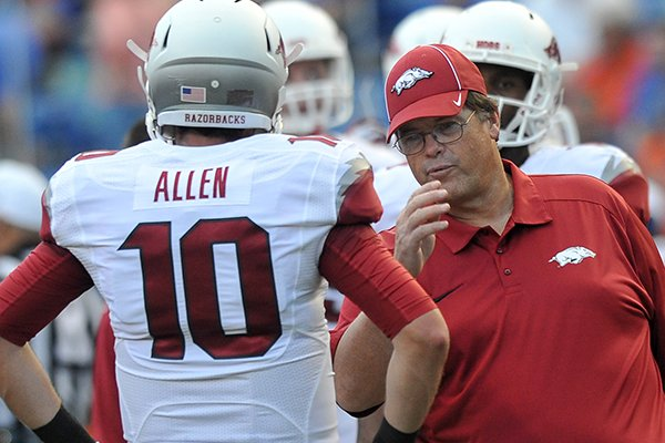 Arkansas offensive coordinator Jim Chaney talks with quarterback Brandon Allen before the start of Saturday night's game at Ben Hill Griffin Stadium in Gainesville, Fla.