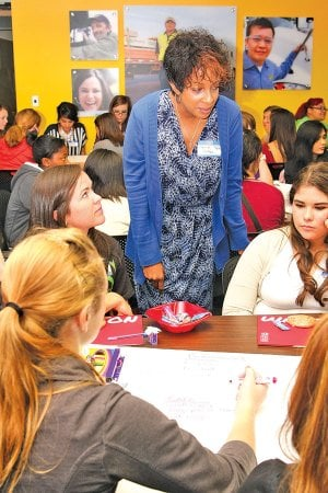 Lorie Cotten of Walmart, center, brainstorms Wednesday with girls attending the Girls in IT conference at J.B. Hunt Transport Services in Lowell. Local businesswomen served as mentors for the girls during the meeting which was meant to expand students' knowledge of jobs in computer science and information science fields.