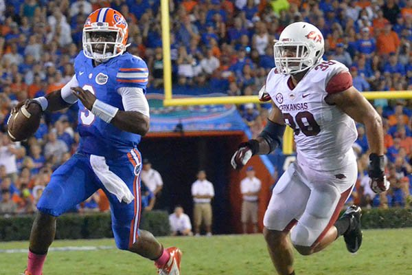 Arkansas defender Jarrett Lake chassis Florida quarterback Tyler Murphy out of the pocket during Saturday night's game at Ben Hill Griffin Stadium in Gainesville, Fla.