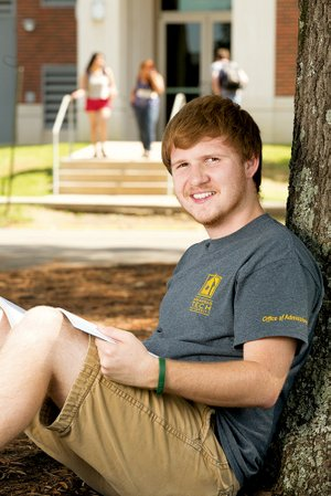 Clay Wyllia of Atkins, a senior at Arkansas Tech University in Russellville, sits under a tree on campus. Wyllia, who works in the Office of Admissions as a tour guide, said he was excited to hear this fall that a record enrollment of 11,000 was reached at the school. Wyllia is Student Government Association president this year.