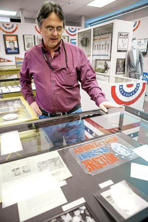 Mike Polston, director of the Museum of American History in Cabot, looks over the collection of memorabilia from the original dedication and the 25th anniversary of the dedication of the Greers Ferry Dam.