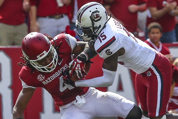 South Carolina's Jimmy Legree, right, forces a fumble out of Arkansas's Keon Hatcher after a 50 yard gain by Hatcher in the third quarter of their game Saturday afternoon in Fayetteville.
